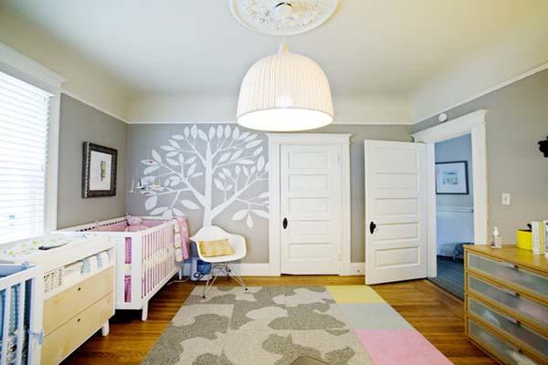 Ağaç şeklinde bir duvar çizimi ile süslenmiş modern bebek odası tasarımı