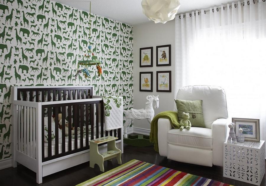 Duvardaki hayvan figürleri ve yeşil ve mavinin uyumuyla bezenmiş sevgi dolu bir bebek odası.
